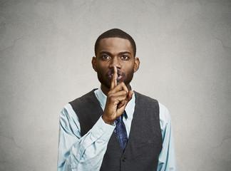 Portrait Secret man, finger on lips gesture grey wall background