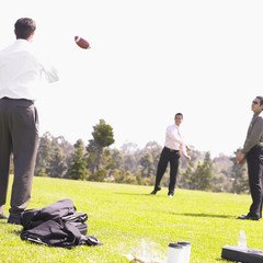Businessmen throwing football in park