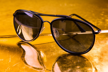 Luxury aviator sunglasses on golden background
