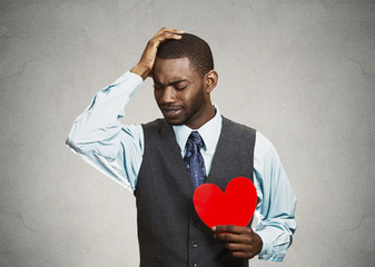 Sad company man holding red heart, crying, grey wall background
