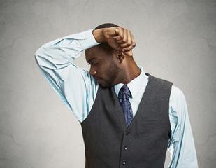 Man smells his armpit, bad odor, grey wall background
