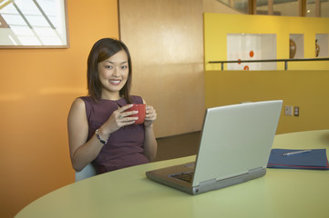 Businesswoman drinking coffee while using a laptop