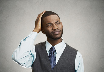Confused man looks up on gray background