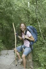 Female hiker resting on a tree stump