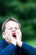 boy outdoors without upper two teeth with pain in the face