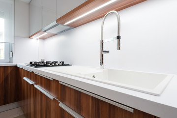 Sink with tap on white worktop in contemporary kitchen