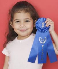 Portrait of girl holding blue ribbon
