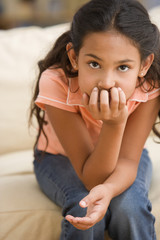 Young girl thinking while resting her chin in her hand