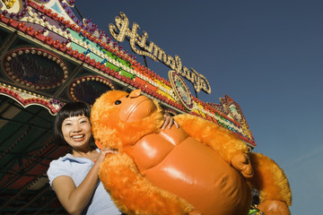Young woman holding a stuffed animal at a carnival