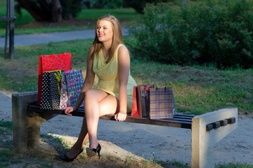 Beautiful woman sitting in the park after shopping