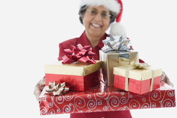 Senior Hispanic woman holding stack of gifts