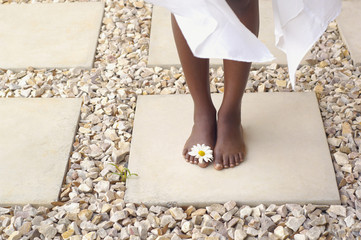 Close up of African American woman's bare feet with flower