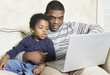 African American father and young son with laptop on sofa