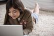 Young Hispanic girl lying on the floor with laptop