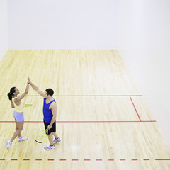 Man and woman high fiving on Squash court
