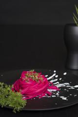 pink spaghetti, black place setting