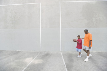 African man and son with basketball on outdoor court