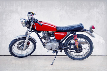 vintage color style of old classic motorcycle standing against w