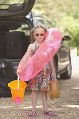 Young girl in flip flops with beach toys