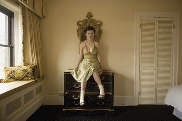 Woman in fancy dress sitting on dresser