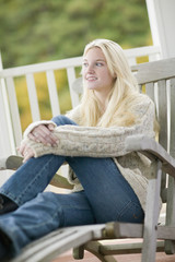 Young woman in sweater sitting on porch