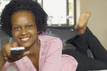Young African woman pointing remote control
