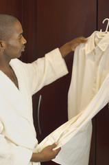 African man looking at shirt on hanger