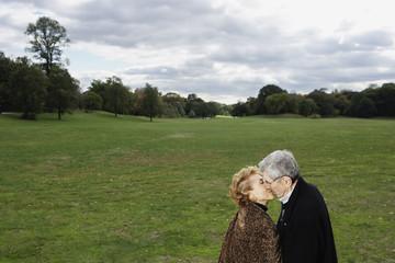 Senior couple kissing in open meadow