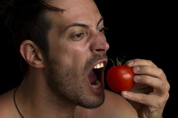 man biting a tomato