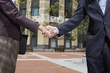 Businesswoman and businessman shaking hands outdoors