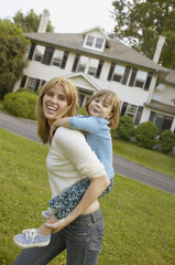 Mother giving young daughter piggyback ride outdoors