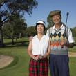 Senior Asian couple smiling on golf course