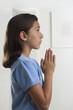 Hispanic girl praying indoors