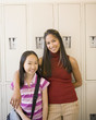 Female teacher with arm around Asian girl in front of school lockers