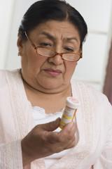Senior Hispanic woman looking at medication bottle