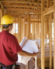 Male construction worker looking at blueprints inside construction site