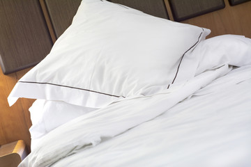 Hotel bed pillow and white sheets