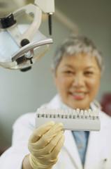 Senior Asian female dentist holding tooth color samples