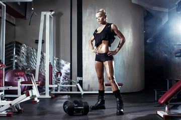 fitness blonde girl prepares for exercises with dumbbells in gym