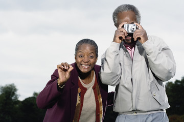 Senior African couple taking photograph outdoors