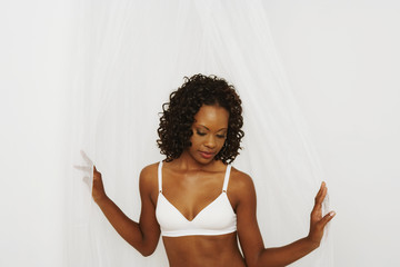 Semi-nude African woman standing in parted curtains