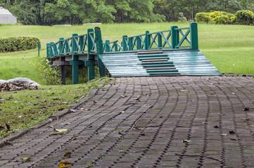 A wooden footbridge across a brook in the park