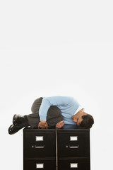 Businessman sleeping on top of filing cabinet
