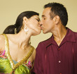 Studio shot of Hispanic couple kissing