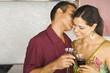 Hispanic couple kissing in kitchen