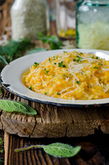 Carrot risotto in the plate on wooden table
