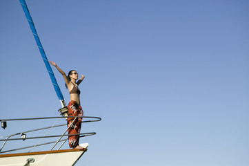 Asian woman on bow of sailboat with arms raised