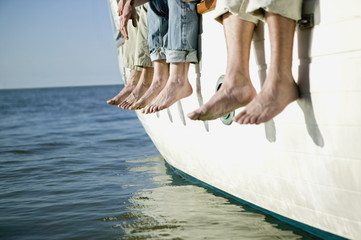 Bare feet hanging over side of boat
