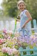 Summer garden - beautiful girl watering roses