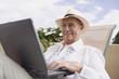 Senior man typing on laptop in lounge chair